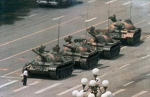 un hombre con una bolsa de la compra se sitúa delante de una columna de tanques en una avenida